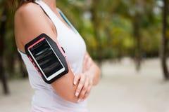 Bracciale d'uso dello smartphone della donna sportiva Immagini Stock Libere da Diritti
