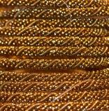 Braccialetti con la fotografia dorata del fondo di colore Fotografia Stock