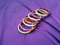 Braccialetti indiani molti braccialetti di colore su fondo viola immagine stock libera da diritti