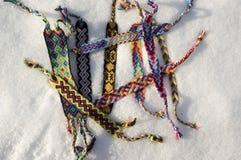 Braccialetti naturali di amicizia in una fila, braccialetti tessuti variopinti di amicizia, fondo della neve, colori dell'arcobal fotografia stock