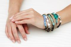 Braccialetti sulle mani di una bella donna con il manicure Fotografie Stock Libere da Diritti