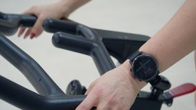 Braccialetto alto vicino di forma fisica sul polso di addestramento della donna di sport sulla bici di esercizio in palestra stock footage