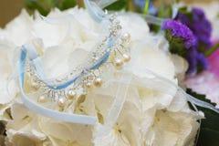 Braccialetto d'argento con le perle ed i nastri blu sui fiori Immagine Stock