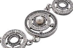 Braccialetto d'argento con le perle su un fondo bianco Immagine Stock