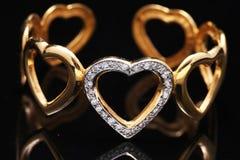 braccialetto dell'oro con i cuori fotografia stock