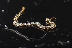 Braccialetto dell'oro con le pietre su un fondo di plastica nero Immagini Stock Libere da Diritti