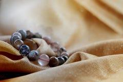 braccialetto della pietra del rutilo dei capelli minerali variegati lussuosi del quarzo o di Venere sul fondo dorato del tessuto Fotografie Stock