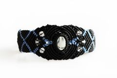 braccialetto nero sulla mano del filo incerato, delle perle di plastica e della pietra di luna nella tecnica di macramè immagine stock libera da diritti