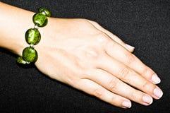 Braccialetto verde smeraldo verde sulla mano della donna Fotografia Stock