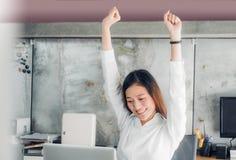 Braccio asiatico di aumento della donna di affari su che allunga davanti allo scrittorio per Immagine Stock