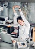 Braccio asiatico di aumento della donna di affari su che allunga davanti allo scrittorio per Fotografie Stock Libere da Diritti