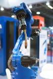 Braccio automatico del robot che funziona nell'ambiente industriale fotografie stock libere da diritti