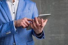 Braccio dell'uomo d'affari facendo uso del dispositivo digitale Fotografia Stock