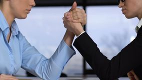 Braccio di ferro femminile dei colleghi sulla tavola, concorrenza di carriera, conflitto di affari stock footage
