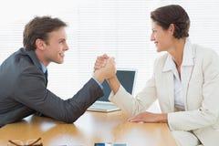 Braccio di ferro sorridente delle coppie di affari alla scrivania Fotografia Stock