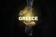 Braccio due che tiene una parola della Grecia Fotografia Stock