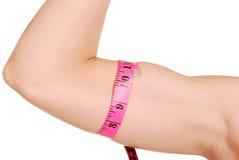 Braccio femminile con la misura di nastro intorno a bicep Fotografie Stock Libere da Diritti