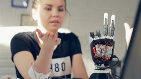 Braccio prostetico elettronico di comandi femminili facendo uso di tecnologia di bionica video d archivio