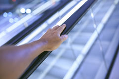 Braccio in una scala mobile automatica in un centro commerciale immagine stock