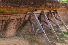 Braced wooden bracing. Laterite wall Royalty Free Stock Images
