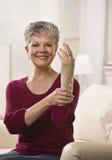bracehand som sätter kvinnan Arkivbild