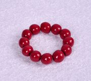 Bracelet avec les boules en bois rouges sur un fond abstrait Images stock