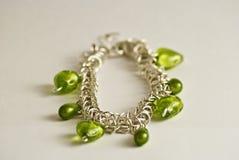 Bracelet avec les coeurs verts Photographie stock