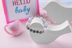 Bracelet with baby name. On wooden bird Royalty Free Stock Photography