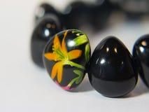 Bracelet black colorful hand. On a white fotne Royalty Free Stock Photo