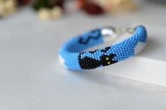 Bracelet bleu avec l'image des chats noirs et blancs Images libres de droits