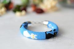 Bracelet bleu avec l'image des chats noirs et blancs Photographie stock