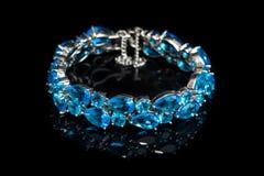 Bracelet with blue stones  on black, close-up Stock Photos
