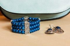 Bracelet, boucles d'oreille et sac à main Image stock