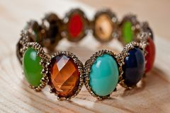 Bracelet of bright colored stones on a wooden background stock image
