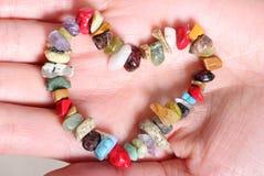 Bracelet coloré en forme de coeur en main de femme Image stock