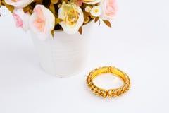 Bracelet d'or avec des diamants et pot de fleurs sur le fond blanc Image libre de droits