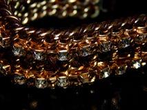 Bracelet d'or avec des pierres sur un fond noir Image stock