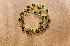 Bracelet d'or avec l'émeraude Photographie stock