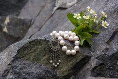 Bracelet de perle se trouvant sur une roche Images libres de droits