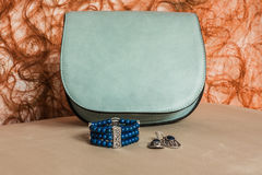 Bracelet, earrings and handbag. In the background, delicate and feminine, trouser suits and dresses Royalty Free Stock Photo