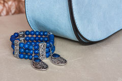 Bracelet, earrings and handbag. In the background, delicate and feminine, trouser suits and dresses Stock Photo