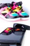 Bracelet et smartphone de forme physique près des espadrilles multicolores de sport D'isolement Images stock