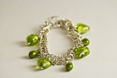 Bracelet with green hearts. Closeup of a bracelet with green pearls Stock Photography