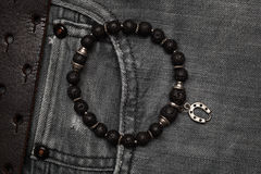 Bracelet on a hand of black stone. Clothing and accessories. black jeans with a leather belt close-up. Royalty Free Stock Photos