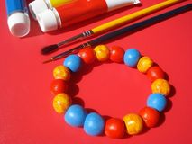 Bracelet of handmade beads. Handmade bracelet, paintbrushes and paint colors Royalty Free Stock Images
