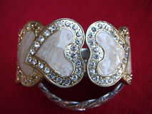 Bracelet heart shape. On red background Stock Images