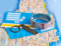 A bracelet, keychain and tickets on the map. Stock Photography