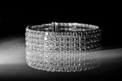 Bracelet made of zirconium. On a shiny glass surface Royalty Free Stock Image
