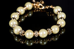 Bracelet of pearls on a black background Stock Photos