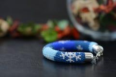 Bracelet perlé bleu avec des images des flocons de neige sur un fond foncé Photographie stock
